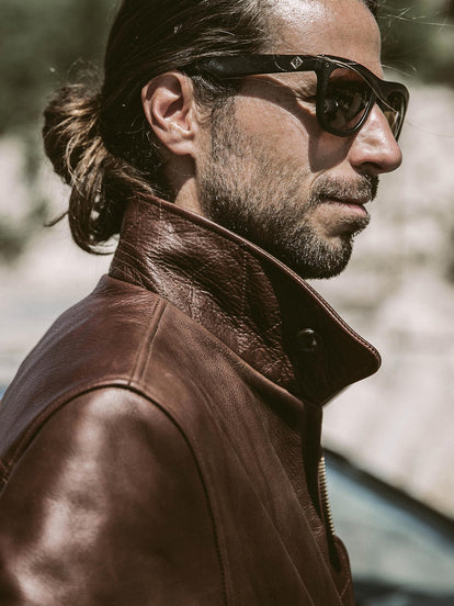Side profile of the right shoulder on a popped-collar leather jacket.