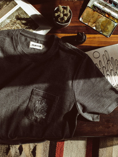 A small potted cactus shot from above with a heavy bag tee that has an illustrated cactus on the breast pocket. Underneath the tee are a coffee table book and a sketch book.