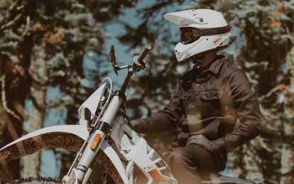 A moto rider in denim jacket and white helmet, paused on a forest trail.
