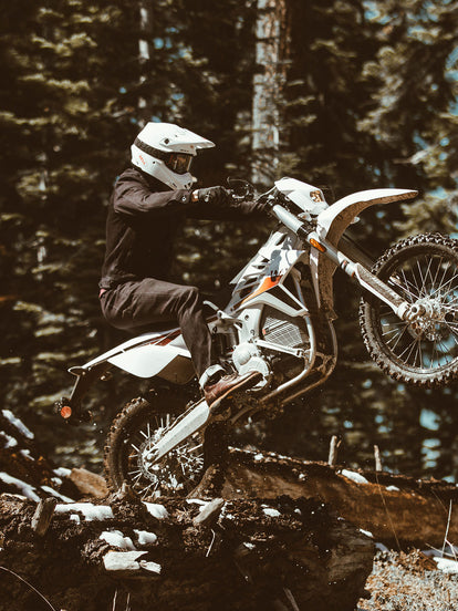 A moto rider pulling a wheelie to hop over a grounded tree trunk.