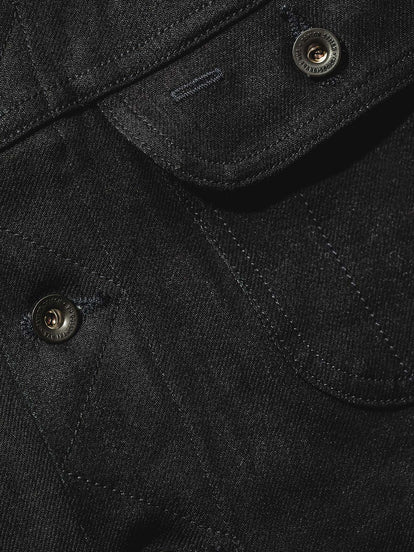 Close up of denim jacket showing pocket and placket stitching detail.