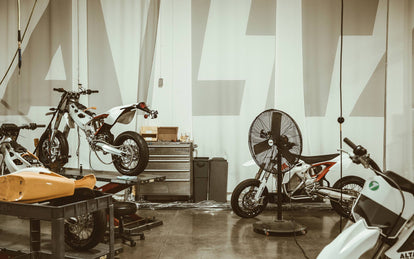 Several bikes under construction, on thw rokshop floor and up on workbenches.