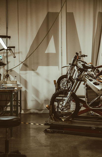 A styled studio set up with two motorbikes and a workbench.