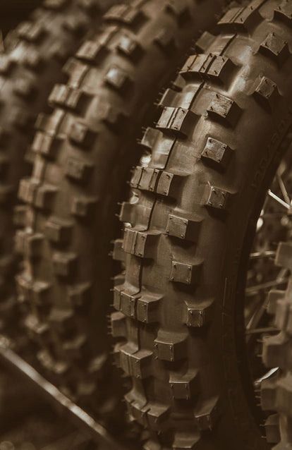 Close up on the tread in a row of three motorocycle tires.