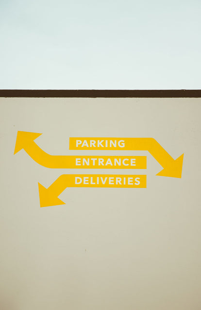 Yellow sign written on a white exterior wall, reading 'parking / entrance / deliveries' with arrows pointing vague directions.