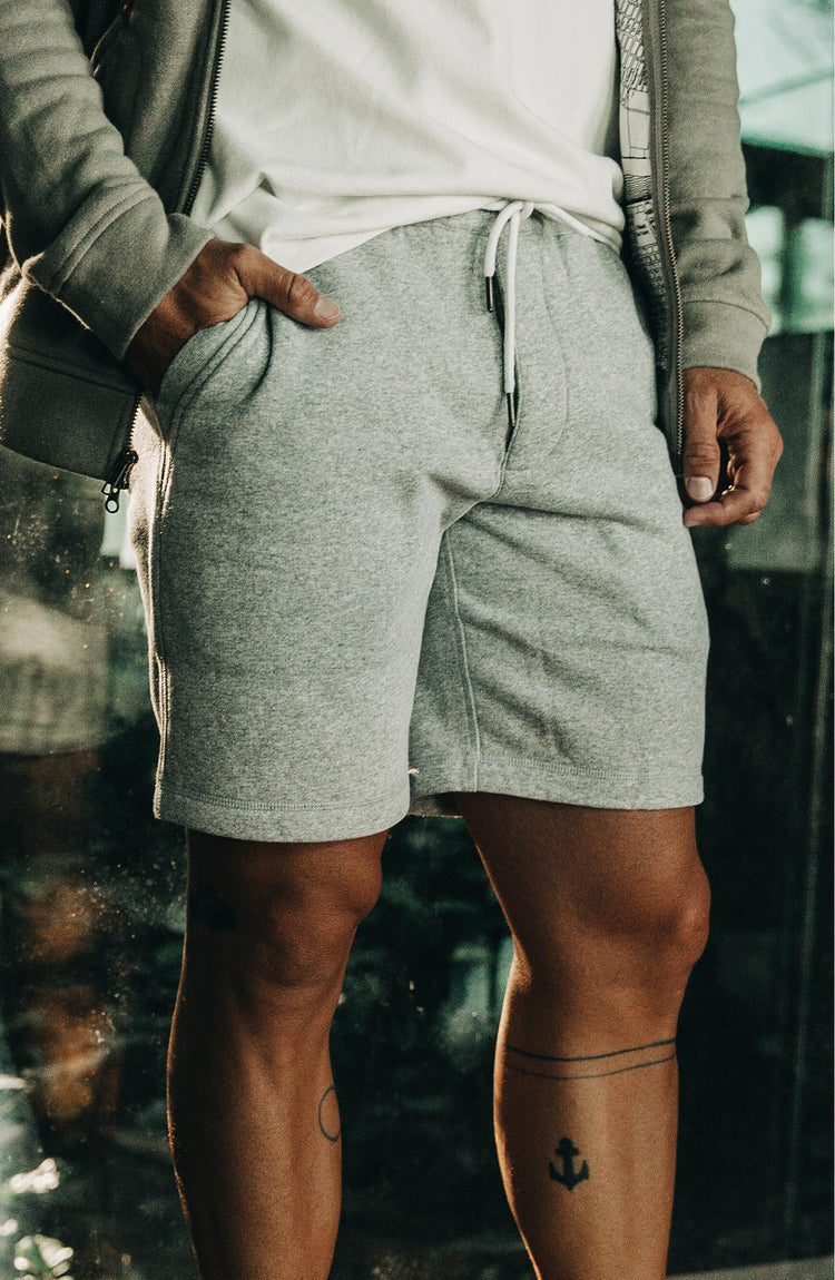 The Heavy Bag Short in Heather Grey Fleece — Model on porch with closeup of shorts with model's hand in left side pocket