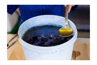 a process shot of the indigo dye in a vat and spoon