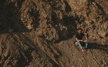 Wide shot of a rocky slope with a lot of scree, our guy sitting barefoot towards the right of frame, wearing jeans and a blue short-sleeved button-down.