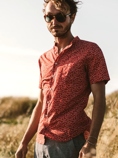 Our guy standing in a field wearing a red floral short sleeve shirt and sunglasses.