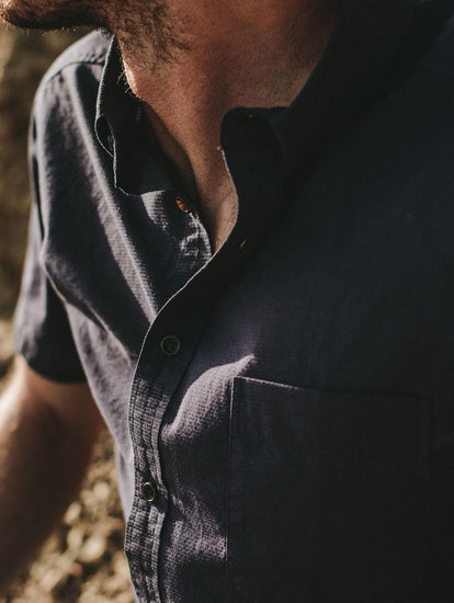 Close up of blue short sleeve shirt front, casually unbuttoned.
