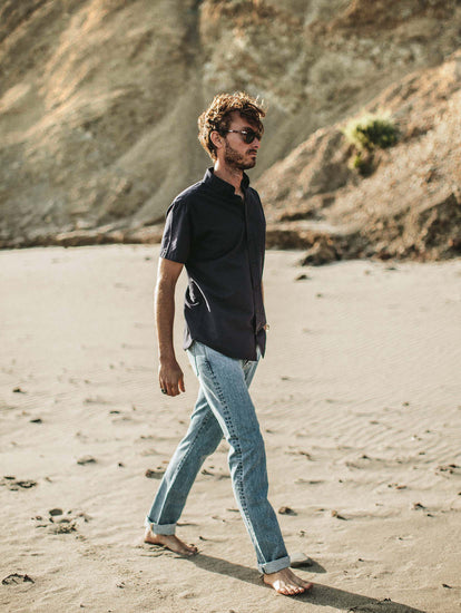 Walking barefoot along the beach with sea cliffs in the background, jeans rolled up and hand in pocket.