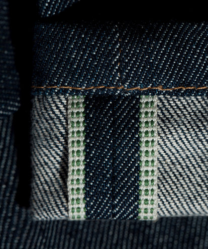 Close up on green-threaded selvage.