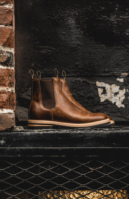 Side shot of a pair of boots against a black-painted brick wall.