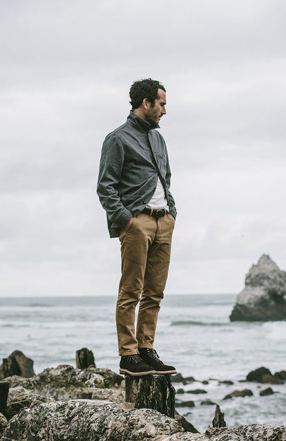 Mikey Armenta standing on a tree stump on the edge of the ocean, looking into the water.
