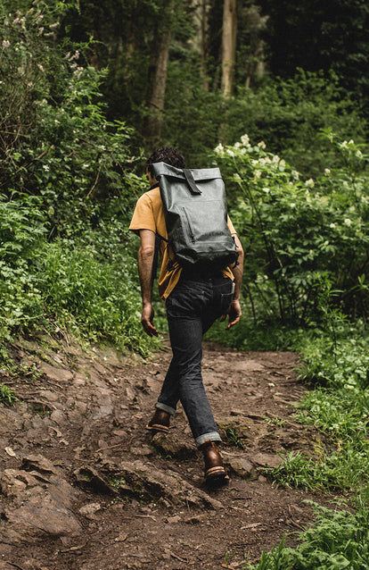 Hiking up a muddy forest trail with a waterproof backpack.
