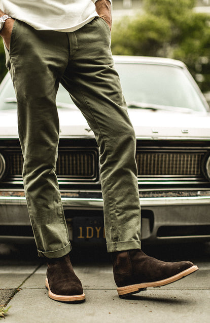 Showing off new suede boots, wearing green chinos, in front of a beat up old car.