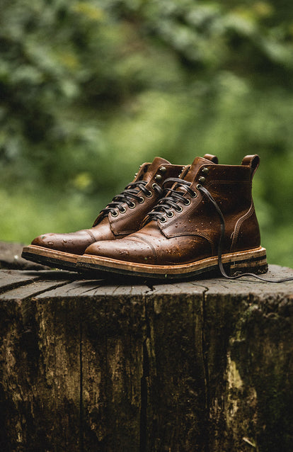 A pair of boots on a tree stump in a wet forest.