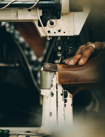 Close up of a boot being stitched on a machine.