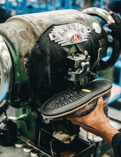 A Vibram sole being machine stitched onto an upper.