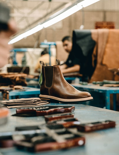 A single finished boot on a workbench, with blurred tools and craftsman.