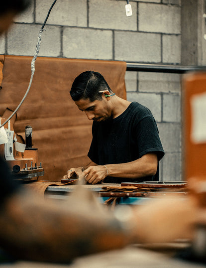 A craftsman at work, obscured by machinery and tools.