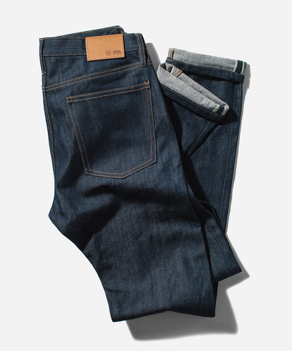 Flat lay of a pair of loosely-folded denim jeans on a white background.