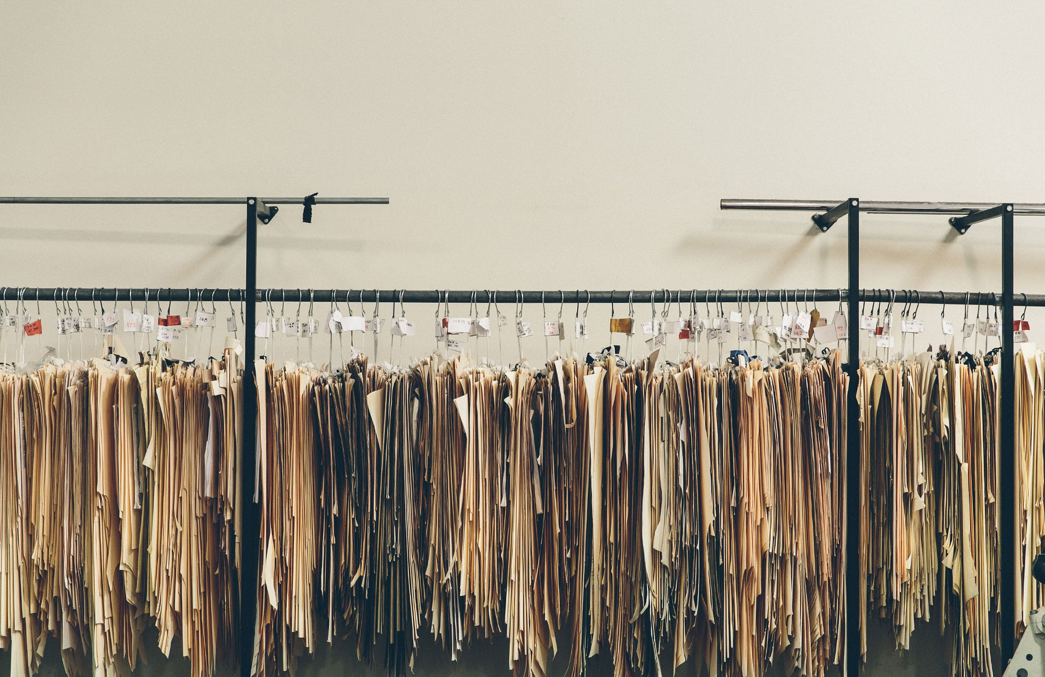 Garment patterns and templates hanging on a rack.