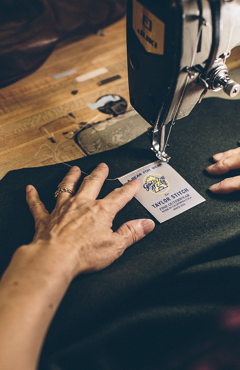 The Golden Bear label being stitched into a garment.