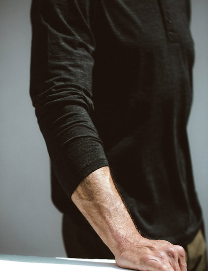 Close-up shot of a model wearing our black merino henley.