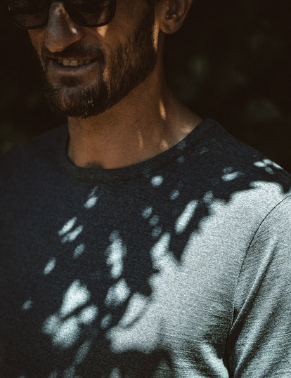 Our guy wearing a blue merino tee, dappled in shadow.