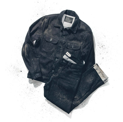 Flat lay of a dyneema denim jacket and jeans on a white background, dusted with dirt.