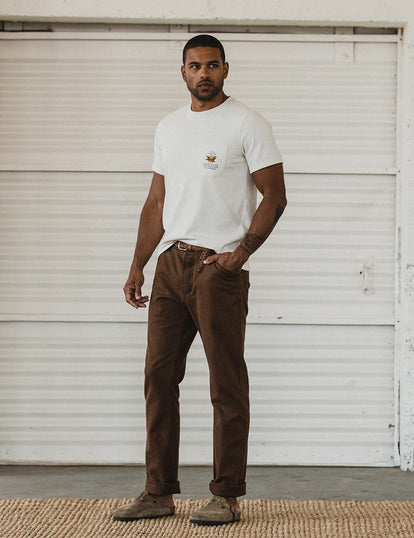 Our guy in tee and workwear pants in front of a white-painted garage door.