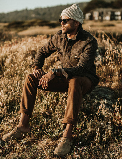 Our guy in a long haul jacket and workwear pants, sitting in a sunny field.
