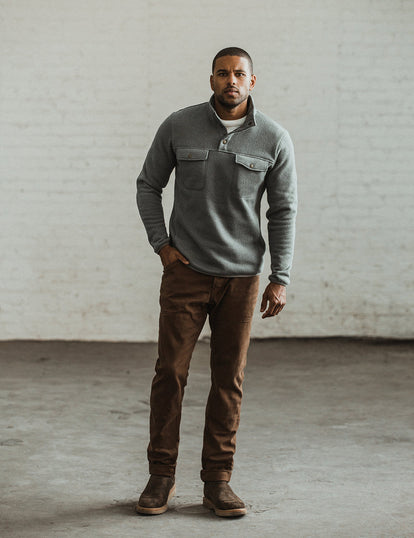 Our guy modeling the workwear pants in a well lit industrial interior.