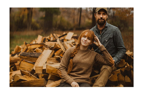 Kate & Josh near posing next to chopped lumber