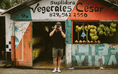 A photo of someone taking a photo right back, standing in the doorway of a roadside fruit shack.