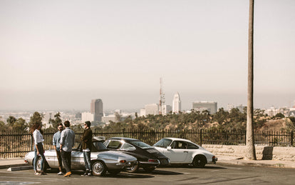 Four or five guys, standing around their parked classic cars, talking, with the city in the far distance.