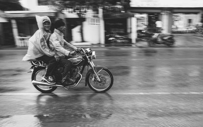 Two guys on a motorcycle, in the rain.