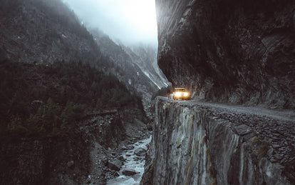 A 4x4 traversing an impossibly-engineered cliffside track through rugged mountains.
