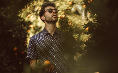 Our guy picking oranges in a floral short sleeved shirt.