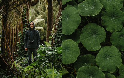 Mike Armenta deep in a wet forest, surrounded by greenery, hood up, getting rained on.