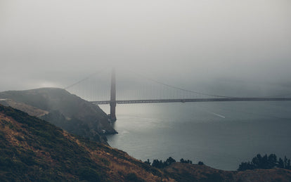 Moody shot of the Golden Gate bridge, surrounded in fog.