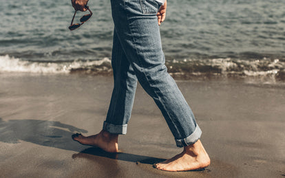 A guy's legs, walking barefoot down the beach in rolled up denim.