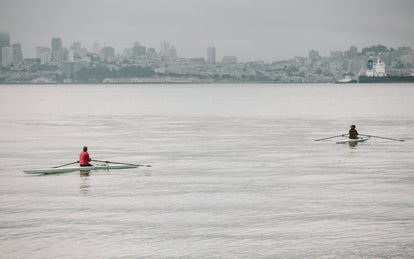 Two people rowing through the bay with SF in the background.