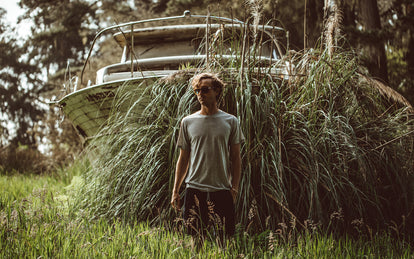 Our guy standing in tall grass, in front of an overgrown trailered cabin cruiser.