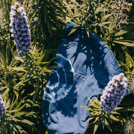 outdoor material shot of The Botanical Dye Tee in Indigo, in bed of plants