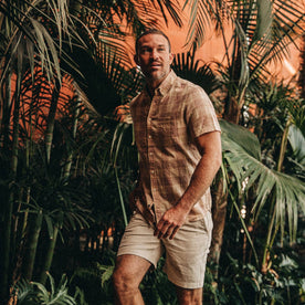 fit model wearing The Short Sleeve Jack in Red Madras, greenery behind