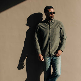 our fit model wearing The Jack in Olive Slub Chambray—against a wall, looking right