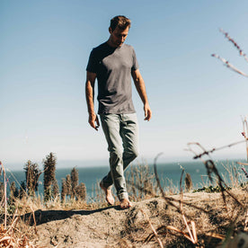 our fit model wearing The Slim Jean in 24-Month Wash Japanese Selvage—walking on the beach, looking down