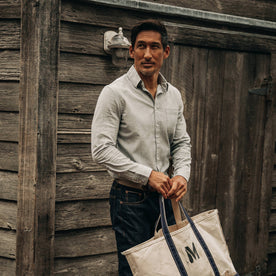 fit model wearing The California in Midnight Slub Micro Stripe, holding bag near wood wall